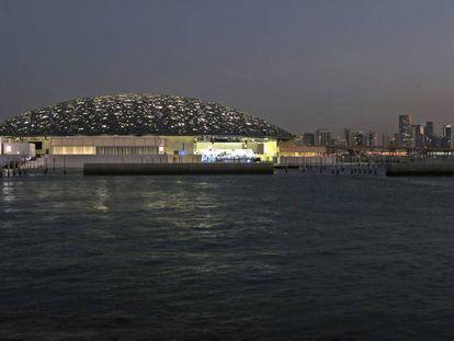 Vista nocturna del Louvre de Abu Dabi con los rascacielos de la capital emiratí al fondo.