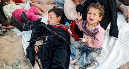 Una familia de refugiados sirios espera entre la frontera de Siria y Turquía.