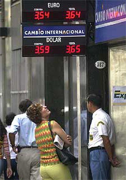 Una ciudadana consulta los valores ante una oficina de cambio.