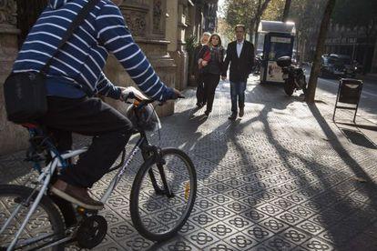 Un ciclista atraviesa esta mañana una acera de Barcelona.