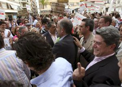 El diputado del PP Federico Trillo (d), detrás del presidente de la Generalitat Valenciana, Francisco Camps, reacciona tras ser increpados por simpatizantes del movimiento