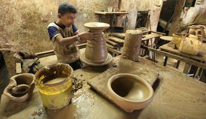 Un joven palestino hace vasijas de arcilla en un taller en Gaza