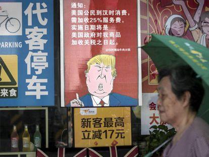 Una mujer pasa junto a un póster que caricaturiza a Trump, en Guangzhou.
