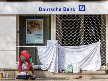 Una persona sin hogar recoge sus pertenencias tras haber pasado la noche en la puerta de una entidad bancaria en pleno centro de Sevilla.