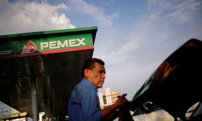 Un hombre reposta en una gasolinera Pemex.