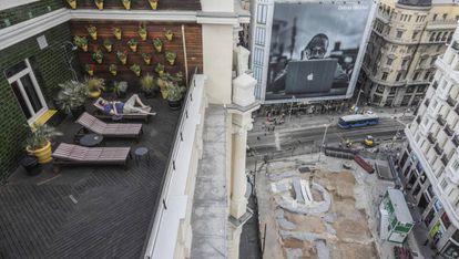 Un vecino de Madrid disfrutaba del verano de 2018 en una terraza desde la que ven las obras en la estación de metro de Gran Vía.