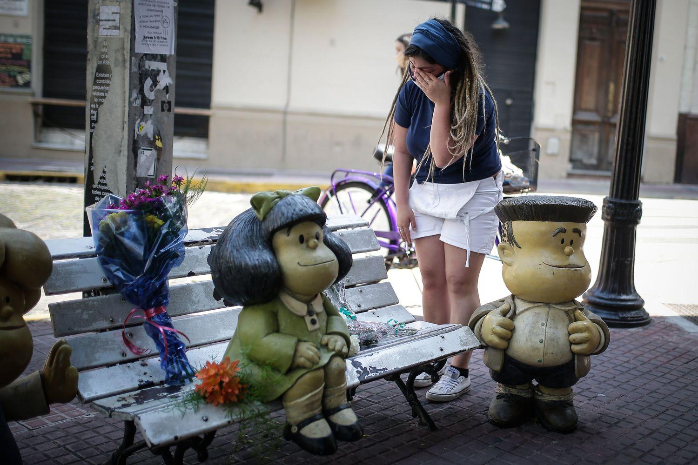 Una mujer llora este miércoles mientras deja flores en la estatua de los personajes de Quino en Buenos Aires.