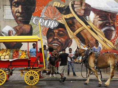 Unos niños alrededor de un carro tirado por caballos con productos para la venta ambulante, en Baltimore (EE UU).
