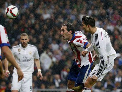 El defensa del Atlético Godín intenta despejar de cabeza ante Cristiano Ronaldo en el último derbi de Copa