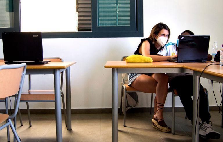 Una voluntaria enseña a un alumno a utilizar un ordenador en el colegio Corpus Christi de Sevilla.