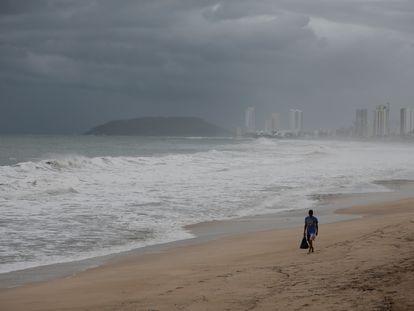 Un hombre camina este martes en una playa de Mazatlán, en Sinaloa, cerrada ante la inminente llegada del ciclón tropical Pamela.