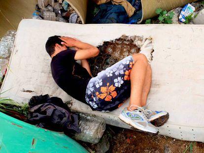 Un menor descansa en un colchón roto en un descampado en Melilla.
