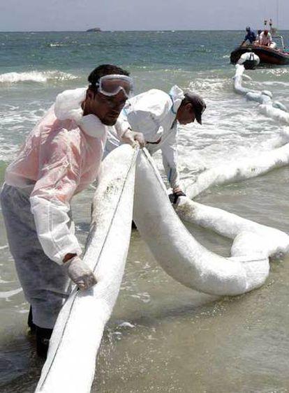 Operarios colocan barreras absorbentes en la playa ibicenca de En Bossa para contener el fuel.