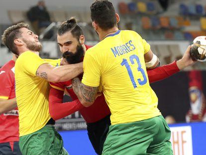 Jorge Maqueda (centro) trata de superar a dos jugadores brasileños este viernes en el partido entre España y Brasil en El Cairo.
