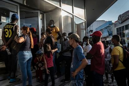 Haitianos y centroamericanos hacen fila para retirar las remesas que les envían sus familiares.