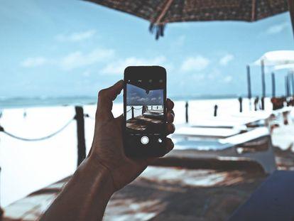Un usuario utiliza un teléfono móvil en la playa.