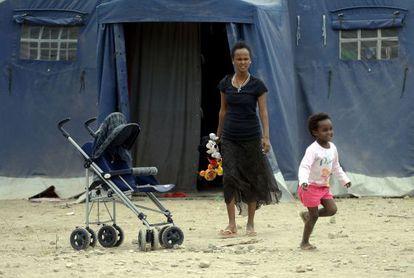 Dos migrantes, este martes en un campamento junto a una estación en Roma.