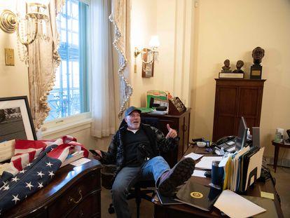 Un manifestante con los pies encima de la mesa de la presidenta de la Cámara de los Representantes, en el Capitolio, en Washington (EE UU).