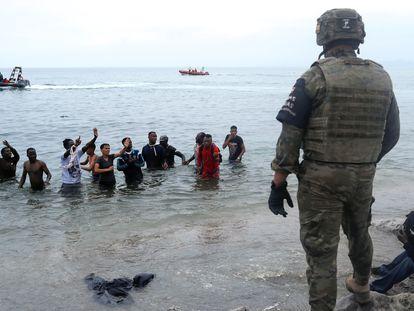 Un militar español frente a un grupo de marroquíes que intentan entrar en Ceuta a través del mar.