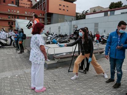 Una periodista de televisión entrevista a profesionales sanitarios frente al Hospital Vall d'Hebron el pasado 12 de mayo.
