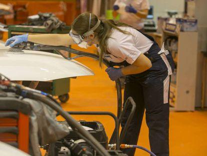 Una estudiante de Formación Profesional pinta un vehículo.