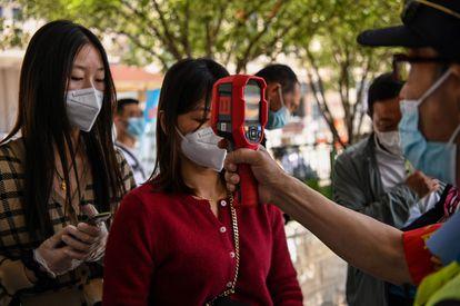 Un control de temperatura a pasajeros recién apeados en la estación de tren de Hankou, en Wuhan.