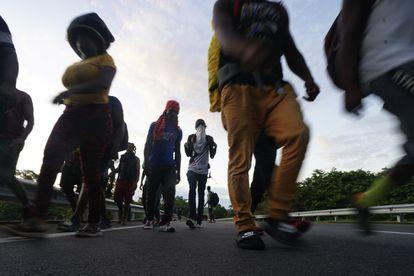 Migrantes haitianos caminan por la carretera en Huixtla, en Chiapas.