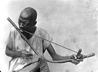 Un hombre tocando el arco musical.