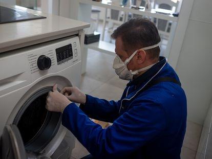 Un técnico repara una lavadora durante el confinamiento.