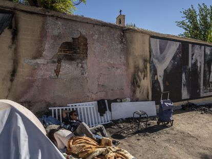 José Camacho, un sintecho nicaragüense que vive en la plaza, dormita bajo el mural, destrozado por las quemaduras.