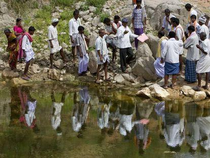 Un grupo de trabajadores rurales junto a un embalse en India.