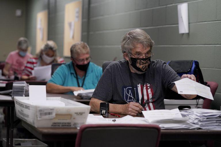 Varios trabajadores clasifican las peticiones del voto por correo, en una oficina en Olathe, Kansas.