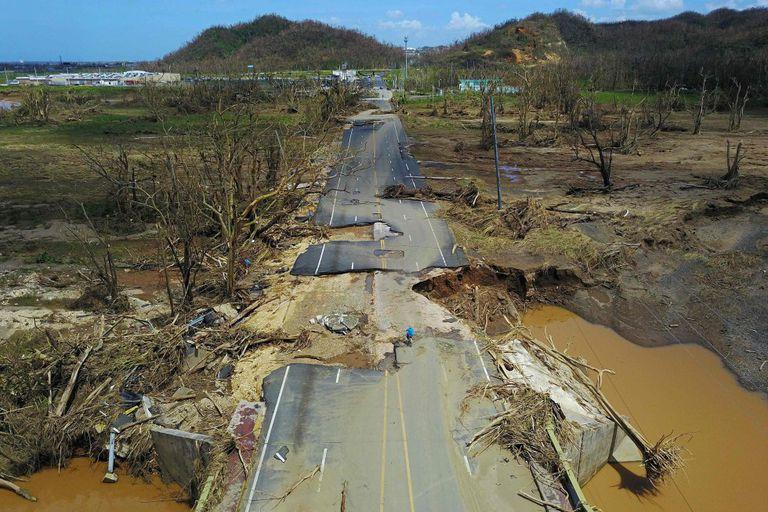 Un hombre se desplaza en bicicleta por una carretera destrozada por el huracán María en Puerto Rico, en septiembre de 2017.