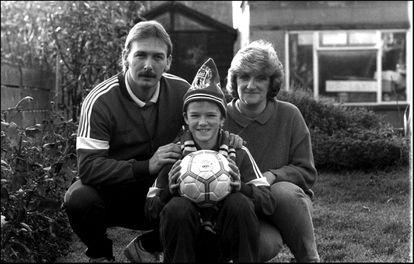 El futbolista David Beckham con sus padres Ted y Sandra, a los 11 años en el jardín de su casa londinense del barrio de Leystone.