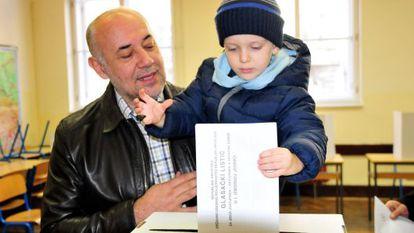 Un hombre vota con su hijo en Zagreb.