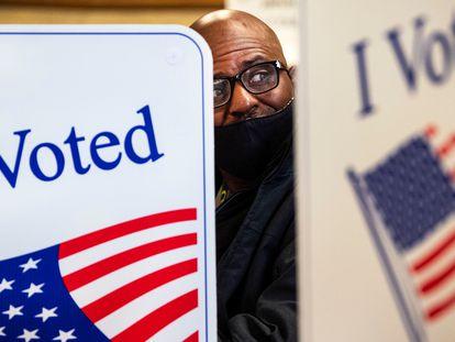 Un hombre llena su papeleta de votación en el centro de votaciones del condado de Cowlitz en Kelso, Washington. En vídeo, las reacciones al resultado de las elecciones.