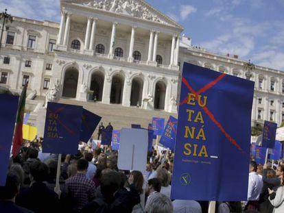 Manifestantes protestan frente al Parlamento de Portugal contral la nueva ley de eutanasia. En vídeo, las reacciones de los diputados.