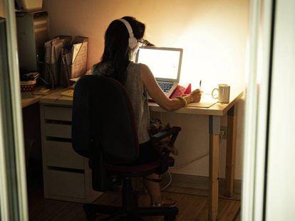 Una mujer teletrabaja para su empresa desde casa.