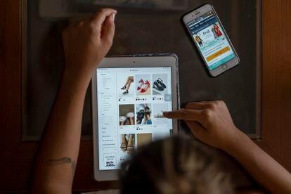Una mujer utiliza una tableta para comprar zapatos por Internet, en una foto de archivo.