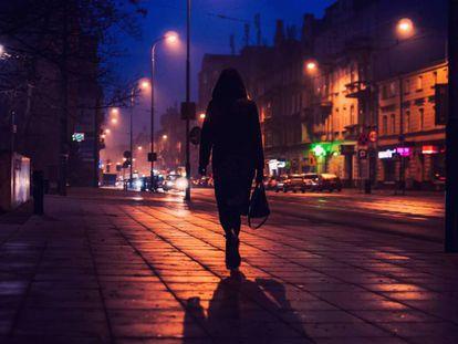 Una mujer camina por una calle, en una foto de archivo.