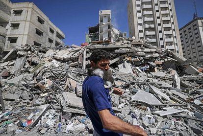 Un palestino, con un gato rescatado entre las ruinas de un edificio bombardeado por Israel, este martes, en Gaza.