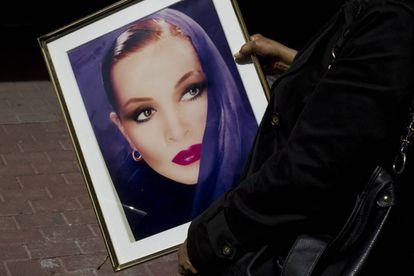 Una mujer sostiene el retrato de Sara Montiel que presidió su coche fúnebre.