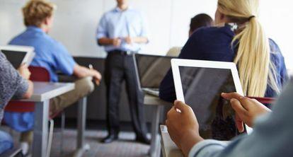 Un estudiante usa una tableta en un aula.