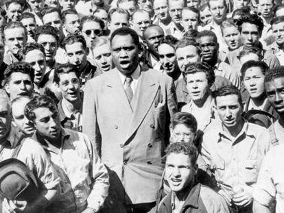 Paul Robeson, rodeado de trabajadores de los astilleros de Oakland (California) interpreta el himno de EE UU, en 1942.