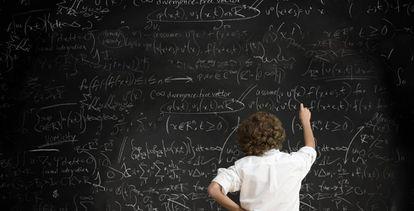 Un chico escribe en una pizarra llena de fórmulas.