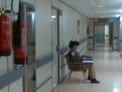 Imagen de una cámara de seguridad en el hospital Virgen del Rocío de Sevilla con una vigilante en un pasillo.