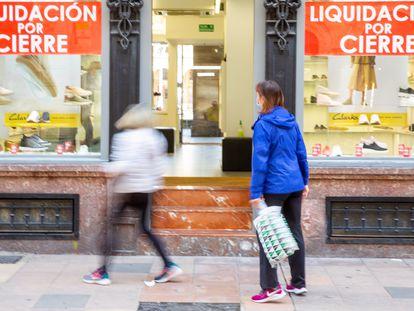 Un comercio del centro de Vitoria con carteles anunciando su liquidación a finales de marzo.