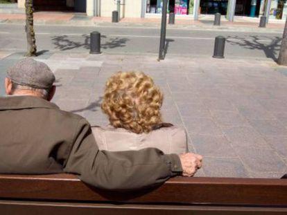 Una pareja de ancianos toma el sol en un banco