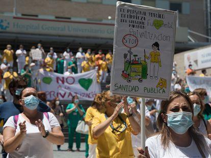 Una trabajadora de limpieza del Hospital Gregorio Marañón sujeta una pancarta que reivindica la importancia de los servicios públicos en Sanidad, el 22 de junio.