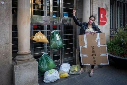 Una vecina coloca bolsas de basura en la puerta de la sede del distrito de Sant Andreu